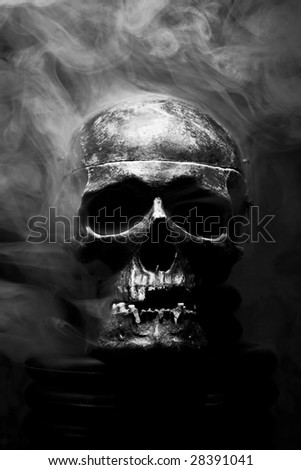 front of real skull in abstract smoke - stock photo