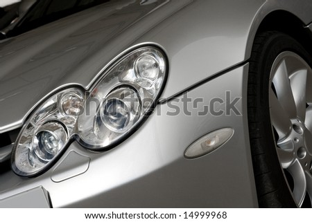 Front of silver super car with xenon headlights - stock photo