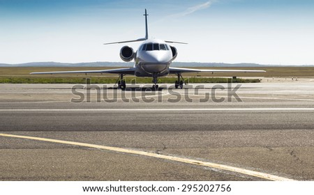 front of the parked private airplane on the runway. white civic, modern jet - stock photo