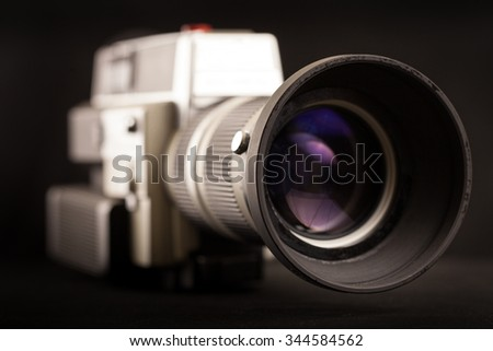 Front  of very old Super 8, focused on the lens using shallow depth of field on black background - stock photo