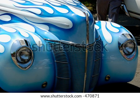 Front of vintage car, white with blue flames paint job