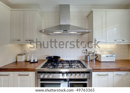 Front on aspect of modern range style cooker with double oven with other kitchen related items standing on a wooden worktop