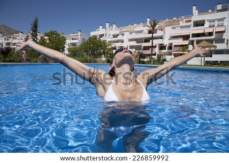 front open arms woman with black goggles in a blue pool - stock photo
