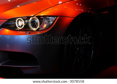 Front part of a coupe sports car under a red spot light. No logo shown. - stock photo