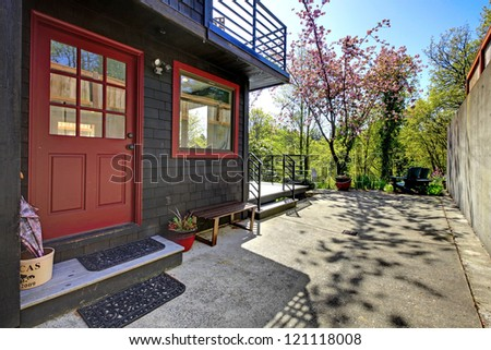 Front red door of black wood house with garden view during spring.