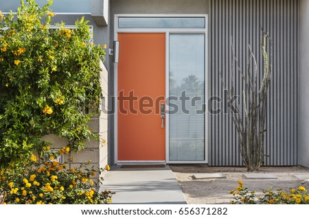 Front reddish orange door, exterior view of a mid-century house