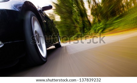 Front side view of black car with heavy blurred motion. - stock photo