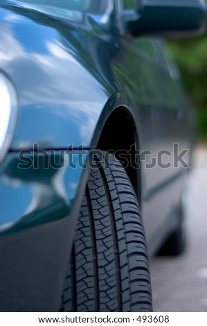 Front tire of a car with the clouds and blue sky reflecting in its fender paint. - stock photo