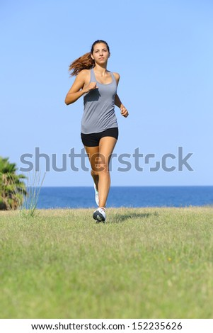 Front view of a beautiful woman running on the grass with the sky and the sea in the background - stock photo