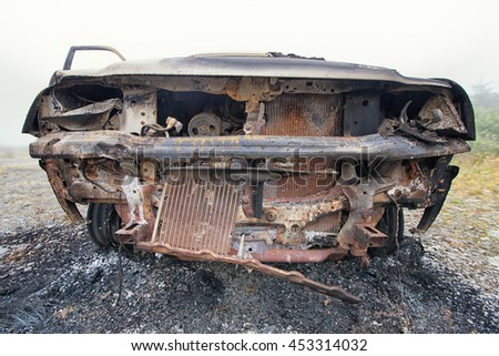 Front view of a burnt out truck left abandoned on common ground.