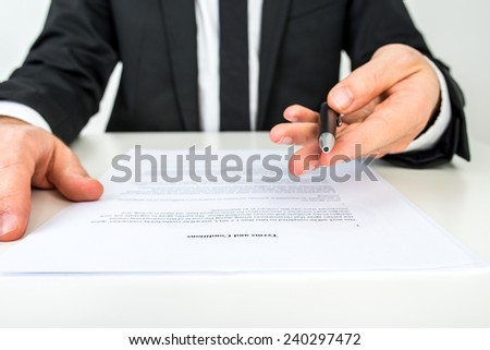 Front view of a businessman offering you to sign a document with focus to the text Terms and Conditions. - stock photo