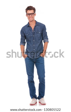 front view of a casual young man standing with his hands in his pockets and smiling to the camera. isolated on a white background - stock photo