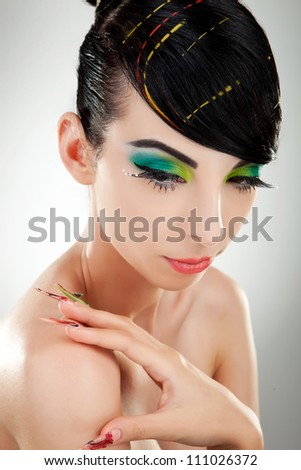 Front view of a glamorous young woman with multicolored make-up and nails watching away from the camera - stock photo