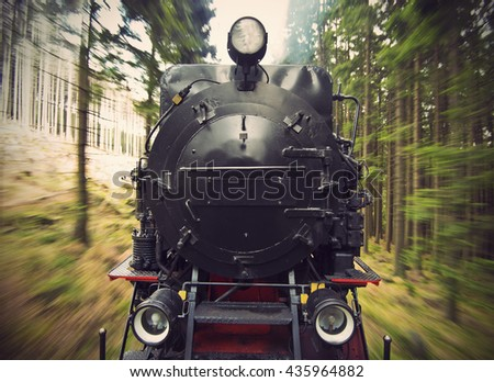 front view of a historic German black steam powered railway train in motion blur, National Park Harz, Germany, Vintage fitlered style - stock photo