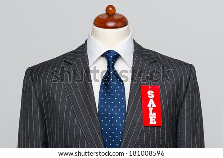 Front view of a Mens grey wool pinstripe suit jacket with blue tie and white shirt on a tailors dummy, sale price tag hanging from the button hole. - stock photo