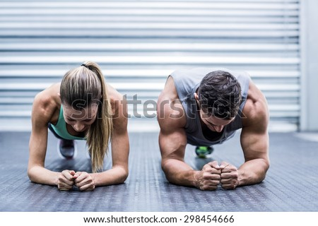 Front view of a muscular couple doing planking exercises - stock photo