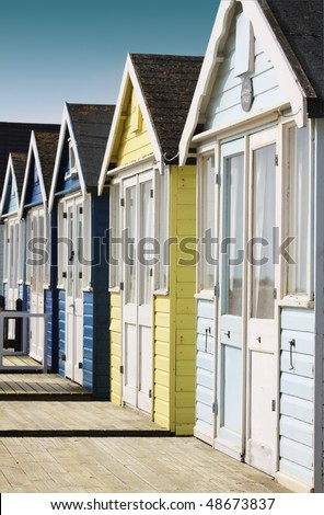 Front view of a row of wooden beach huts with wooden terraces located in Christchurch Hampshire UK. Huts painted in pale blue and yellow colours. - stock photo
