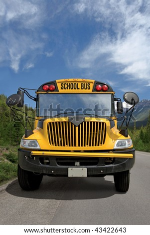 Front view of a school bus on a rural road. - stock photo