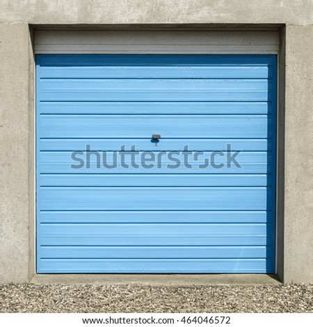 Front View Of A Small Blue Square Garage Door With A Gravel Driveway.
