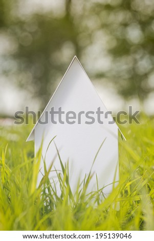 Front view of a small paper model house on a green grass field in spring time. - stock photo