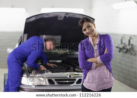 Front view of a smiling client looking at camera in a garage - stock photo