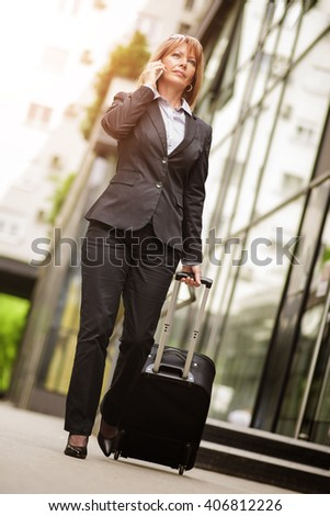 Front view of a traveler woman walking and using a smart phone in an airport - stock photo