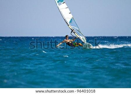 Front view of a windsurfer passing by almost horizontally