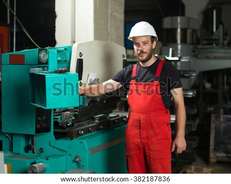 front view of a worker, standing, looking proud, wearing red overalls, and a white protective helmet, operating the control panel of an industrial bending machine, painted in turquoise and white - stock photo