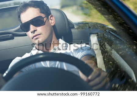 Front view of a young man driving his convertible car - stock photo