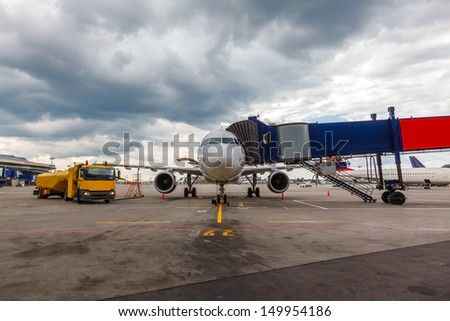 Front view of airplane at gate and gangways for the plane - stock photo