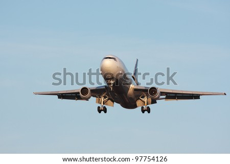 Front view of an aircraft approaching runway - stock photo