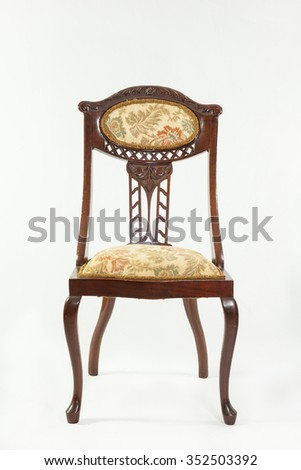 Front view of an antique Art Nouveau mahogany parlour chair with curved flowing lines and carved fruit and flower detail typical of the era over a white background
