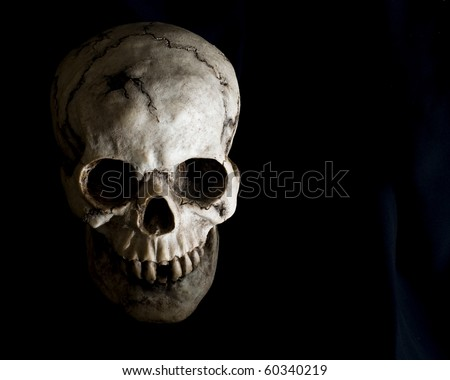 Front-view of an old, cracked and damaged human skull in deep shadow. - stock photo