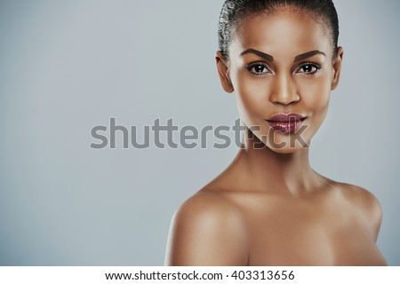 Front view of beautiful African female model with calm expression and bare shoulders over gray background with copy space on one side - stock photo
