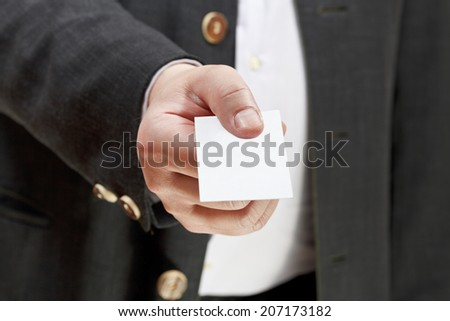 front view of blank white business card in businessman hand close up - stock photo