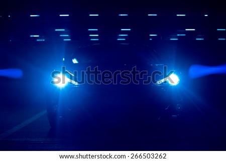 Front View of Bright Blue Modern Car Headlights Illuminated at Night - stock photo