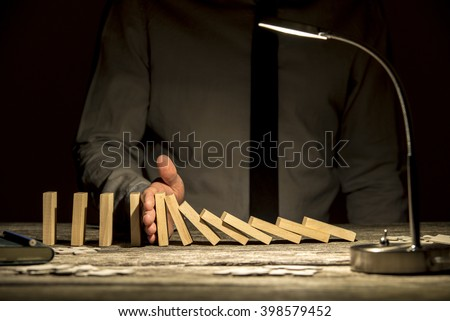 Front view of businessman stopping falling dominos with his hand on wooden textured office desk with a lamp turned on. - stock photo
