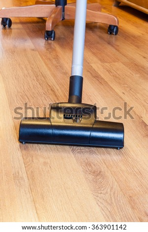front view of cleaning of parquet floor by vacuum cleaner at home - stock photo