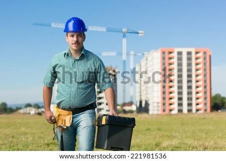 front view of confindent caucasian engineer holding tool box on residential construction site - stock photo