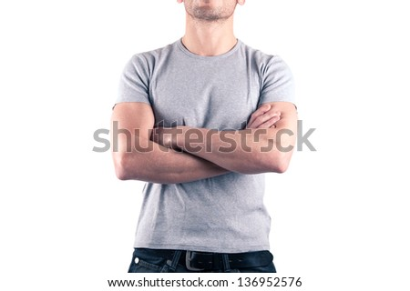 Front view of crossed arms muscular man close up on white background.