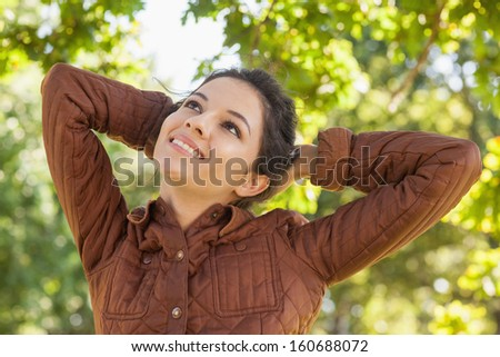 Front view of cute woman posing in a park wearing a brown coat - stock photo