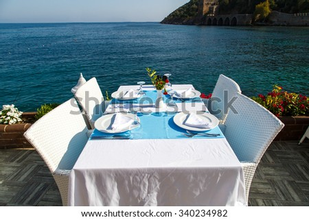 Front view of dinner table with white plates for four on a table with white chairs, with the seascape view.