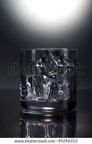Front view of empty scotch glass on grey background
