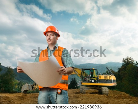 front view of engineer on construction site holding plan - stock photo
