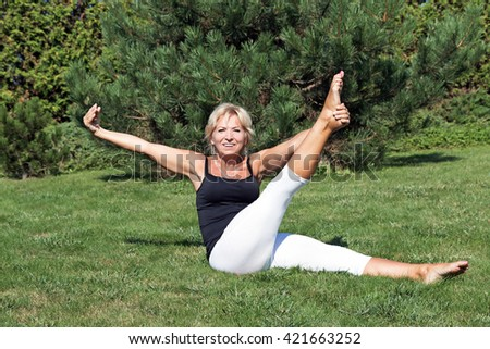Front view of flexible attractive blond senior woman is stretching exercising outdoors. The smiling woman is looking at the camera.  - stock photo
