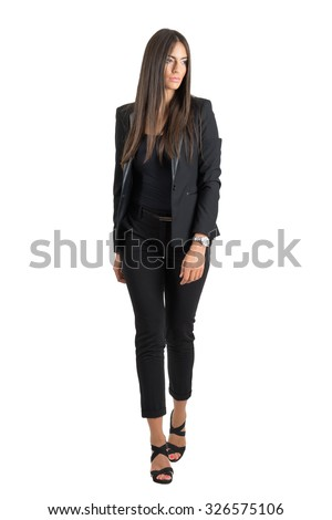 Front view of gorgeous sexy tanned business woman walking looking away. Full body length portrait isolated over white studio background.  - stock photo