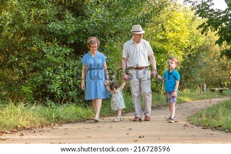 Front view of grandparents and grandchildren walking on a nature path - stock photo