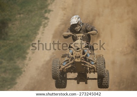 Front view of guad racer jumping. The quad bike and rider are very muddy.Potential trademarks are removed and face of the racer is unidentifiable. - stock photo