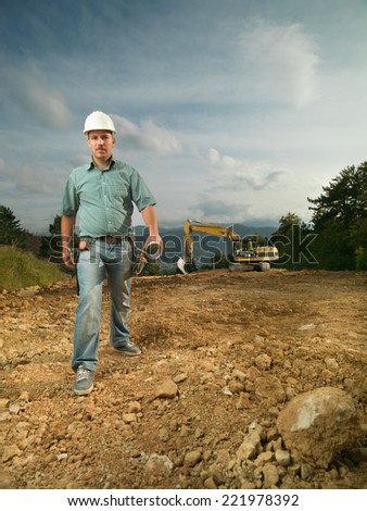 front view of handsome caucasian engineer walking on construction site - stock photo