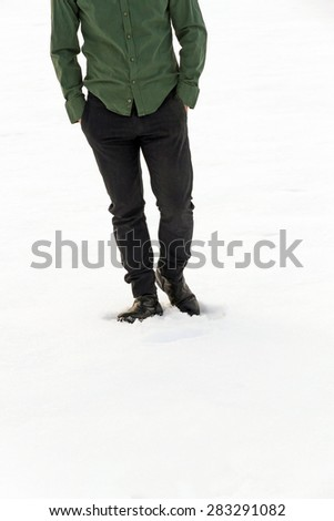 Front view of lower body half-dressed man walking in the snow with his hands in his pockets and green jacket